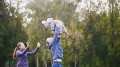 Happy family: Father, Mother and child - little girl walking in autumn park: dad Stock Footage
