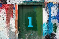 Number 1 door and paint covered wall in ship painters yard Stock Photos