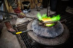 Male foundry worker heating bronze ingot over furnace in bronze foundry Stock Photos
