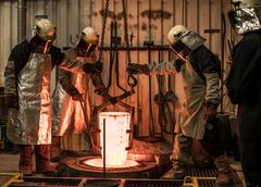 Male foundry workers winching white hot melting pot in bronze foundry Stock Photos