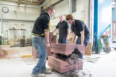 Male foundry workers lifting mould from bronze sculpture in bronze foundry Stock Photos