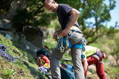 Rock climber on hillside preparing climbing equipment on safety harness Stock Photos