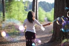 Rear view of woman in forest making bubbles with bubble wand Stock Photos