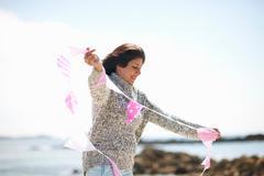 Woman at coast holding bunting Stock Photos
