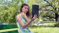 Absorbed girl sitting in the park and browsing something on tablet Stock Footage