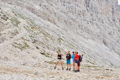 Hikers at bottom of rocky mountain, Austria Stock Photos