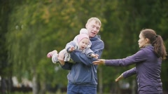 Happy family: Father, Mother and child - little girl walking in autumn park: a Stock Footage