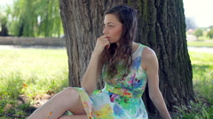 Thoughtful girl sitting under the tree in park and looking thoughtful Stock Footage