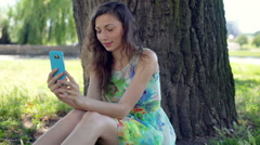 Pretty girl in floral dress doing selfies on smartphone while sitting in the par Stock Footage