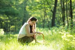 Young woman crouching to forage wild herbs in forest, Vogogna, Verbania, Stock Photos