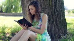 Pretty girl in floral dress reading absrobing book under the tree Stock Footage