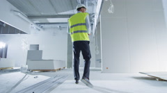 Follow Shot of Engineer in Hard Hat Walking inside Building under Construction. Stock Footage