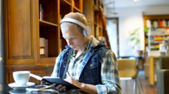 Boy listening music on headphones while reading book in the library Stock Footage