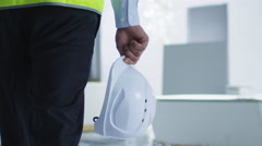 Follow Shot of Engineer Walking on Construction and carrying White Hard Hat Stock Footage