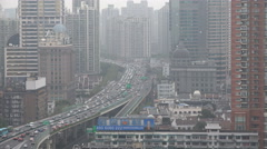 Traffic drives over a major highway, past skysckrapers, central Shanghai, China Stock Footage