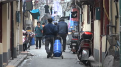 Delivery man walks gas canister through narrow alleys old Shanghai, China Stock Footage