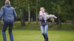 Happy family: Father, Mother and child - little girl walking in autumn park Stock Footage