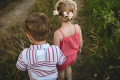 Rear view of young girl and twin brother holding hands in meadow Stock Photos