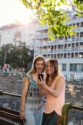 Two adult female friends reading smartphone texts in city, Vienna, Austria Stock Photos