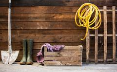 Row of spade, rubber boots and hosepipe by shed Stock Photos