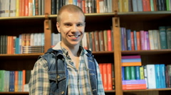 Student standing next to the bookshelves and smiling to the camer Stock Footage