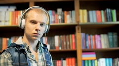 Pensive boy listening music next to the bookshelves and looking to the camera, s Stock Footage