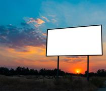 Blank billboard ready for new advertisement with sunset background. Stock Photos