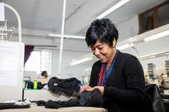 Female factory worker removing stitches from black cloth from speed stitching Stock Photos