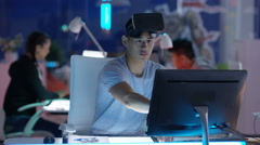 4K Young computer game designer working at his desk & looking into VR viewer Stock Footage