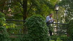 The Red-Haired Man Stands Near to a High Parapet in the Centre of City Park Stock Footage
