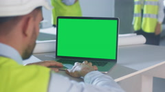 Engineer using Laptop Computer with Green Screen on Construction. Stock Footage