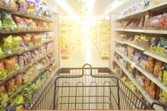 Supermarket aisle with empty red shopping cart background Stock Photos