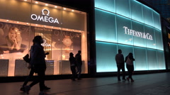 People walk past two brightly lit stores of Western luxury brands in China Stock Footage
