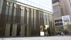 People walk past a golden colored Gucci store in Shanghai, China Stock Footage