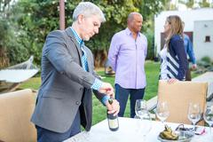 Mature man uncorking wine bottle at garden party table Stock Photos
