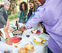 Adult friends helping themselves to food and drink at garden party table Stock Photos
