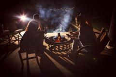 Four mature adults sitting together around patio fire at night Stock Photos