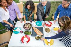 Overhead view of mature adults helping themselves to food and drink at garden Stock Photos