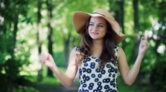 Pretty girl taking off hat and smiling to the camera in the forest Stock Footage