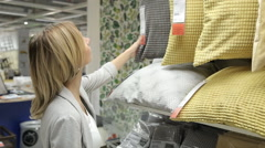 Young woman chose a pillow in a supermarket. Stock Footage