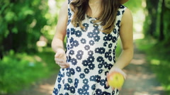 Pretty girl throwing apple from one hand to another and looking thoughtful, stea Stock Footage