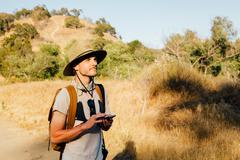 Hiker holding smartphone looking away, Malibu Canyon, California, USA Stock Photos