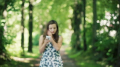 Absorbed girl walking on pathway in the forest and texting on smartphone Stock Footage