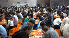 People eat lunch in massive restaurant, trade show Shanghai, China Stock Footage