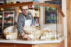 Male worker in bakery, adjusting price ticket in cabinet Stock Photos