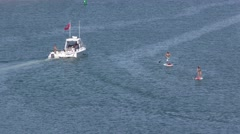 Motorboat being towed with rebel flag flying and two paddle boarders. Stock Footage