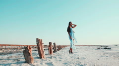 Young, beautiful girl in a blue dress in an unusual place. White and pink salt Stock Footage