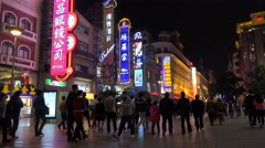 People walk past neon billboards in shopping street Shanghai, China Stock Footage