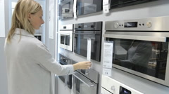 Woman chooses an oven in the shop Stock Footage