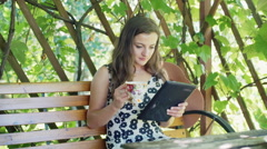 Absorbed girl looking on something on tablet and drinking coffee Stock Footage